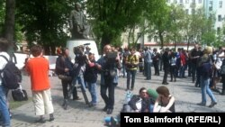 Russian protesters rest on camping mats in front of the statue of Abai in Moscow.