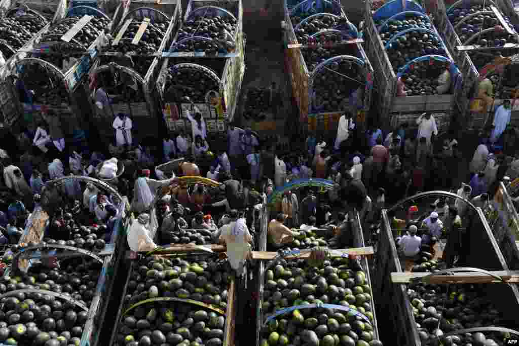 Pakistani farmers gather at a fruit market to sell watermelons in Lahore. (AFP/Arif Ali)
