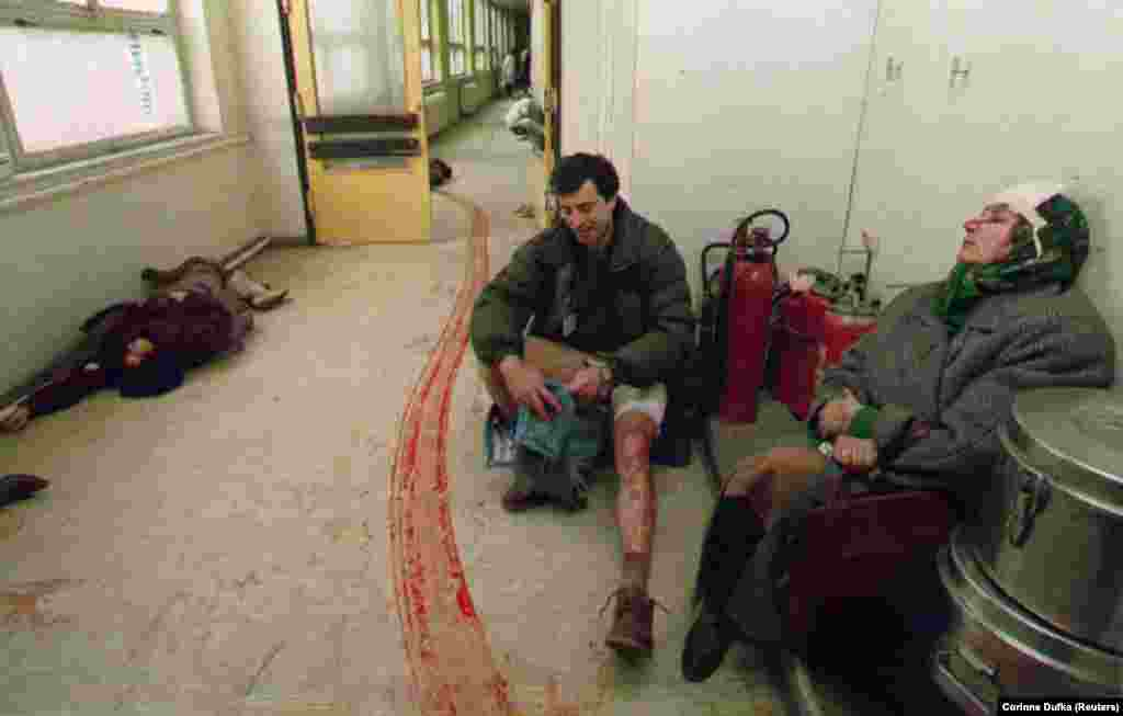 Civilians injured by a mortar in Sarajevo's central market await treatment in a hospital corridor on February 5, 1994. The woman at left died before doctors could attend to her.