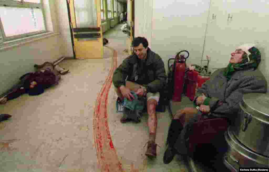 Гражданские лица, пострадавшие в результате обстрела на центральном рынке Сараево, в ожидании медицинской помощи сидят в коридоре больницы. 5 февраля 1994 года. Женщина слева скончалась до того, как медики смогли осмотреть ее.