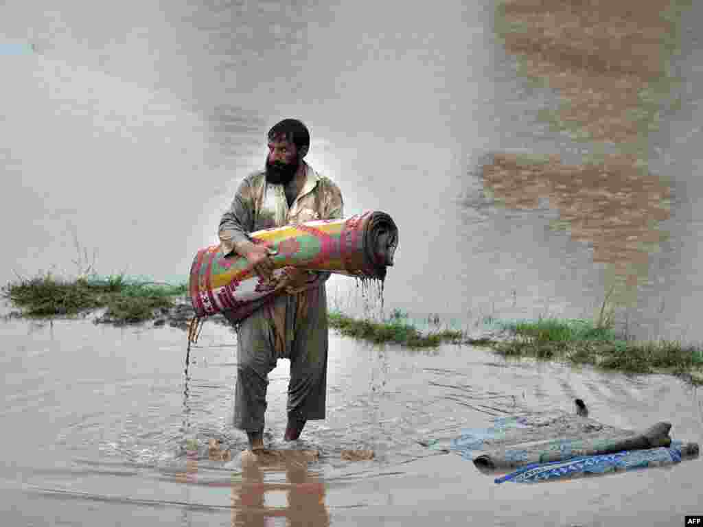 A Pakistani flood survivor attempts to preserve some of his possessions in a waterlogged area of Nowshera. Pakistan faces the risk of a public health disaster, with up to 3.2 million people hit by the worst floods in generations. Photo by A. Majeed for AFP