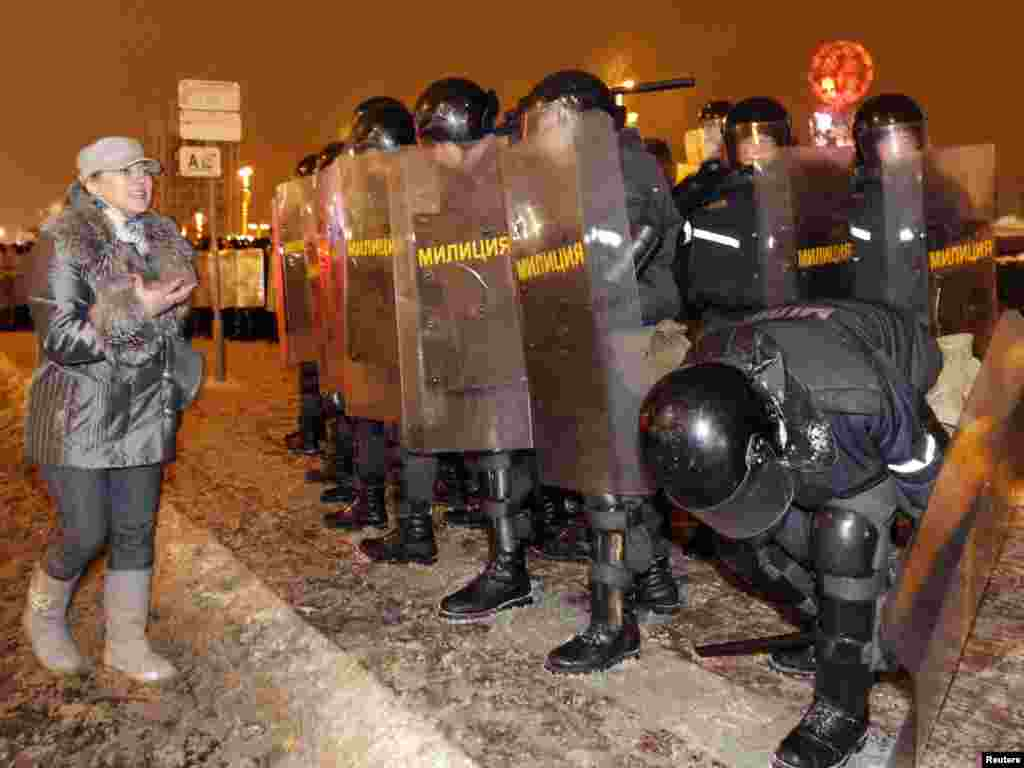 An opposition supporter appeals to riot police for sympathy.