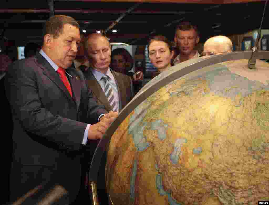"Chavez and Russian Prime Minister Vladimir Putin look at a globe while visiting the Russian Navy's ""Kruzenshtern"" sailing ship in the port of Guaira, near Caracas, in April 2010."