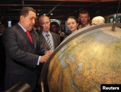 Российский премьер-министр Владимир Путин и президент Венесуэлы Уго Чавес осматривают земной шар во время посещения парусника российского флота Крузенштерн в порту Гуайра близ Каракаса, 2 апреля 2010 года