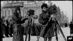 """""""Лесли"""" журналынын сүрөтчүсү Дональд К. Томпсон (солдо) жана АКШ армиясынын капитаны Кингмора Орусиянын Екатеринбург шаарын сүрөткө тартышууда. 1919-жыл."""