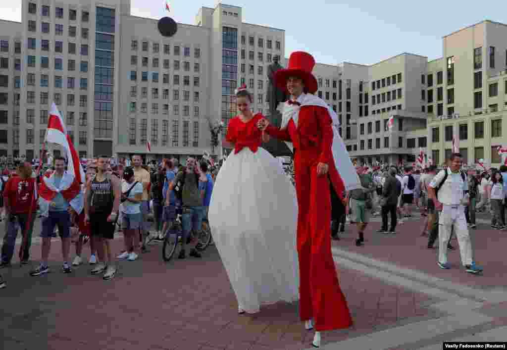Артисты на ходулях, одетые в цвета используемого оппозицией исторического бело-красно-белого флага Беларуси, участвуют в антиправительственной акции протеста в Минске. 16 августа 2020 года.