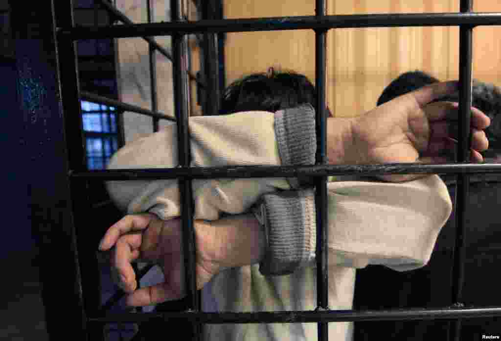 A detained illegal immigrant waits in a holding cell at a police station in Krasnoyarsk.