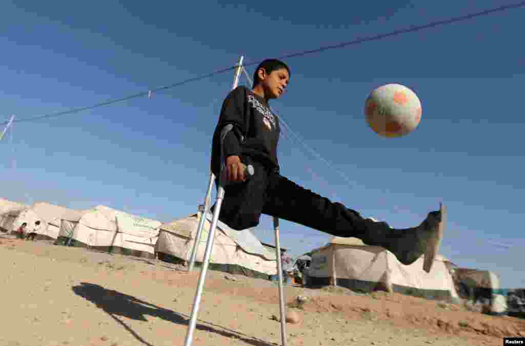Displaced Iraqi boy Jasim Abudllah Jasim, 13, who according to his family lost his leg in an air strike in Baiji, plays soccer in the Debaga camp on the outskirts of Irbil. (Reuters/Muhammad Salem)