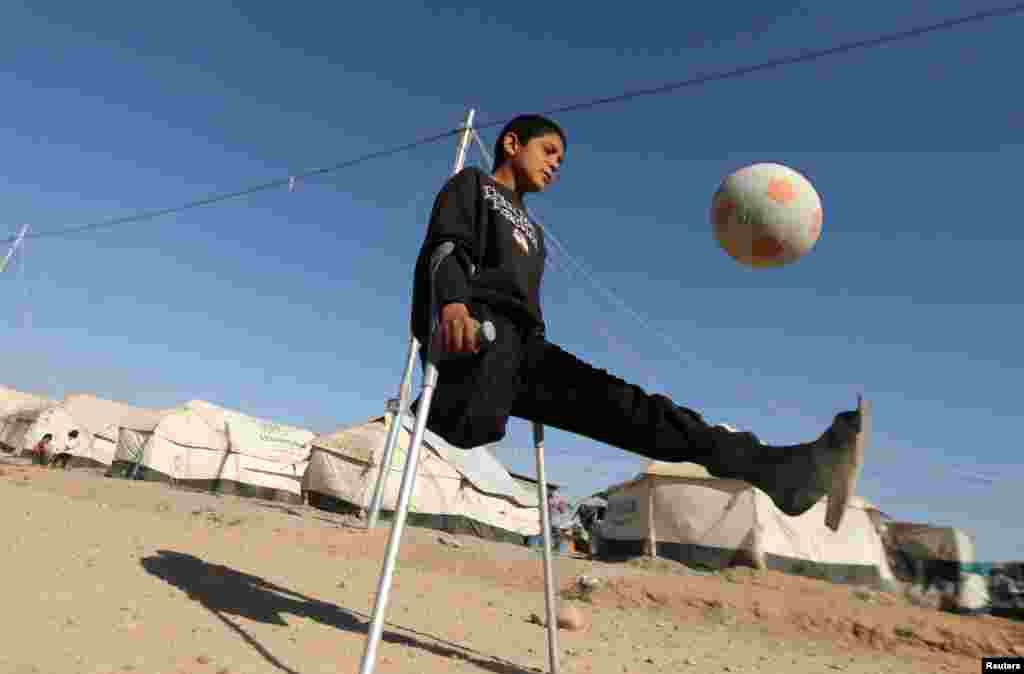 Baýjide urlan howa zarbasynda aýgyny ýitiren 13 ýaşly yrakly Jasim Abudllah Jasim Erbiliň daäyndaky Debaga lagerinde futbol oýnaýar. (Reuters/Muhammad Salem)