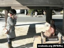 Масумі Камэда (Такійскі Ўнівэрсытэт) перад фігуркай Буды ў Камакуры