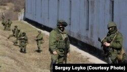 Қырым аннексияланардан бірнеше күн бұрын Украинаның әскери базасы маңында жүрген, белгісіз формадағы Ресей сарбаздары.