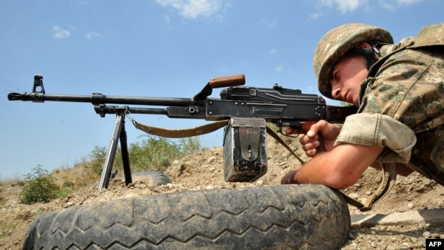 Nagorno-Karabakh -- An Armenian soldier of the self-proclaimed republic of Nagorno-Karabagh aims his Kalashnikov machine gun as he stands in a trench at the frontline on the border with Azerbaijan near the town of Martakert, 06Jul2012