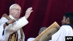 Pope Francis (L) blesses the faithful from the balcony of St Peter's basilica