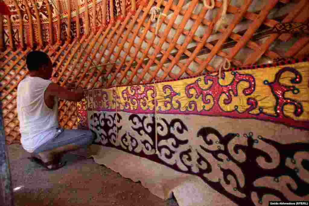 Astara's eldest son, Dulat, one of nine children, helps to decorate the inside of the yurt.