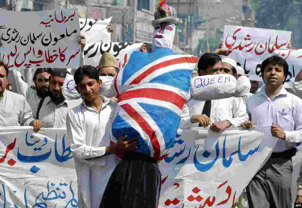 A man displays an effigy of Queen Elizabeth as he marches with others during an anti-British protest in Lahore, Pakistan in June 2007, shortly after the honor was announced for Rushdie.