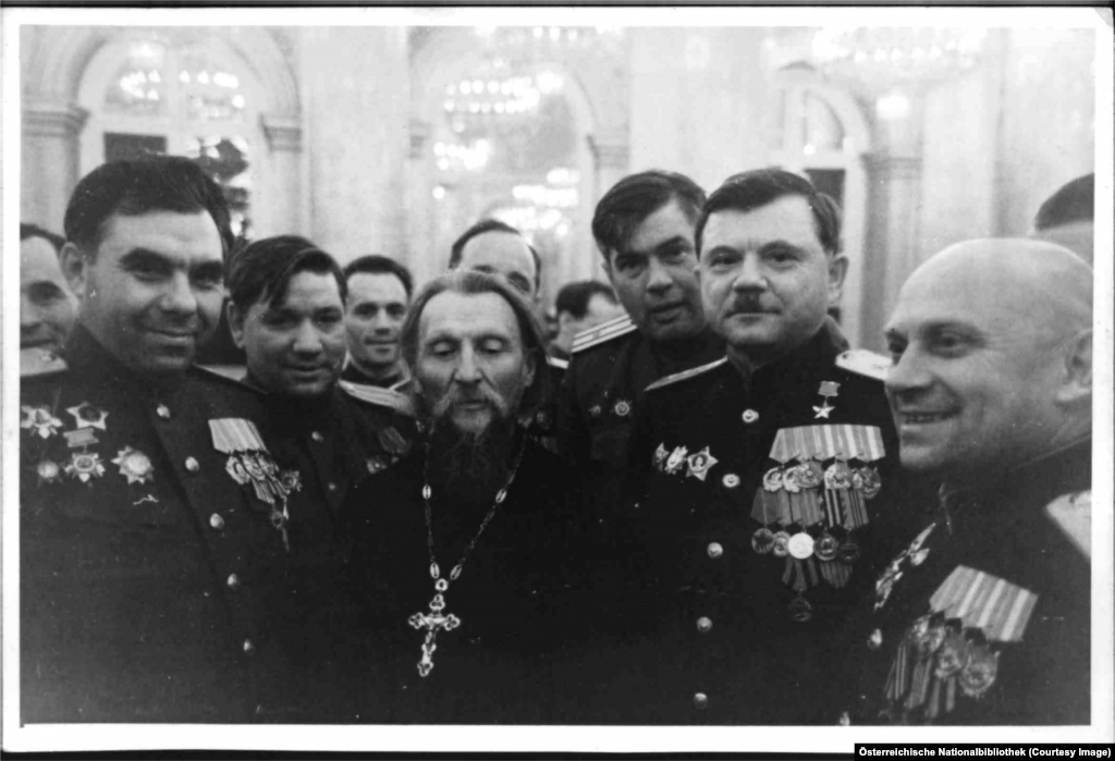 An Orthodox priest outblinged by a group of Soviet generals.
