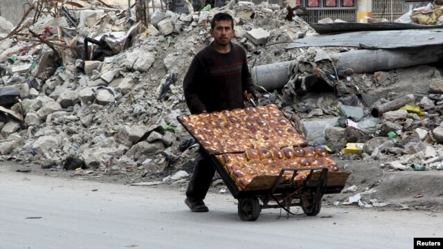A man selling pastries walks past the rubble of damaged buildings in the rebel held al-Shaar neighborhood of Aleppo on February 10.