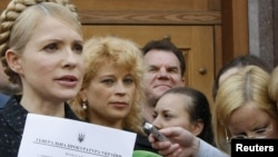 Opposition leader Yulia Tymoshenko shows reporters a summon for a May 17 meeting with investigators, as she leaves the general prosecutor's office in Kyiv on May 12.