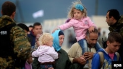 Migrants board a train after crossing the border between Macedonia and Greece on September 8.