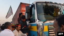 Supporters of Imran Khan's PTI party check the documents of a truck driver at an unofficial checkpoint in a bid to block NATO supply trucks in Peshawar on December 4.