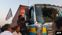 Pakistan -- Supporters of Imran Khan, head of Pakistan Tehreek-e-Insaf (PTI) party, check the documents of a truck driver at an unofficial checkpoint in a bid to block the NATO supply trucks in Peshawar, December 4, 2013