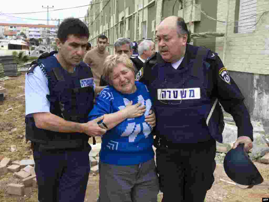 """ISRAEL, Sderot : Israeli policemen help an Israeli woman in shock following a rocket attack from Gaza on the southern Israeli town of Sderot December 29, 2008. Israel bombed Gaza for a third day in an """"all-out war"""" on Hamas, as tanks massed on the border and the Islamists fired deadly rockets to retaliate for the blitz that has killed nearly 320. Sderot, located next to the Palestinian territory, is regularly targeted by Gaza militants."""