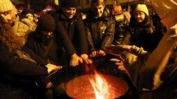 Ucraineni protestând duminică seara în fața birourilor lui Zelenski în Kiev.