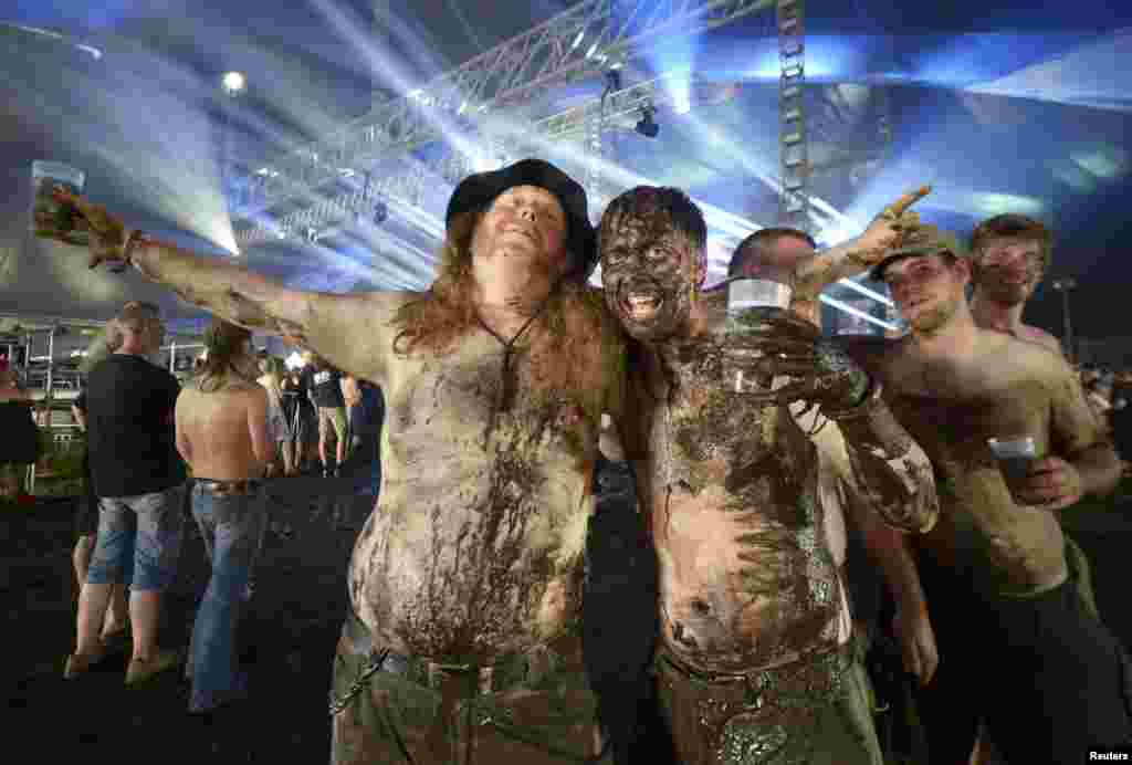 Heavy-metal fans covered with mud pose for photographers during the 24th Wacken Open Air Festival in Wacken, Germany. (Reuters/Fabian Bimmer)