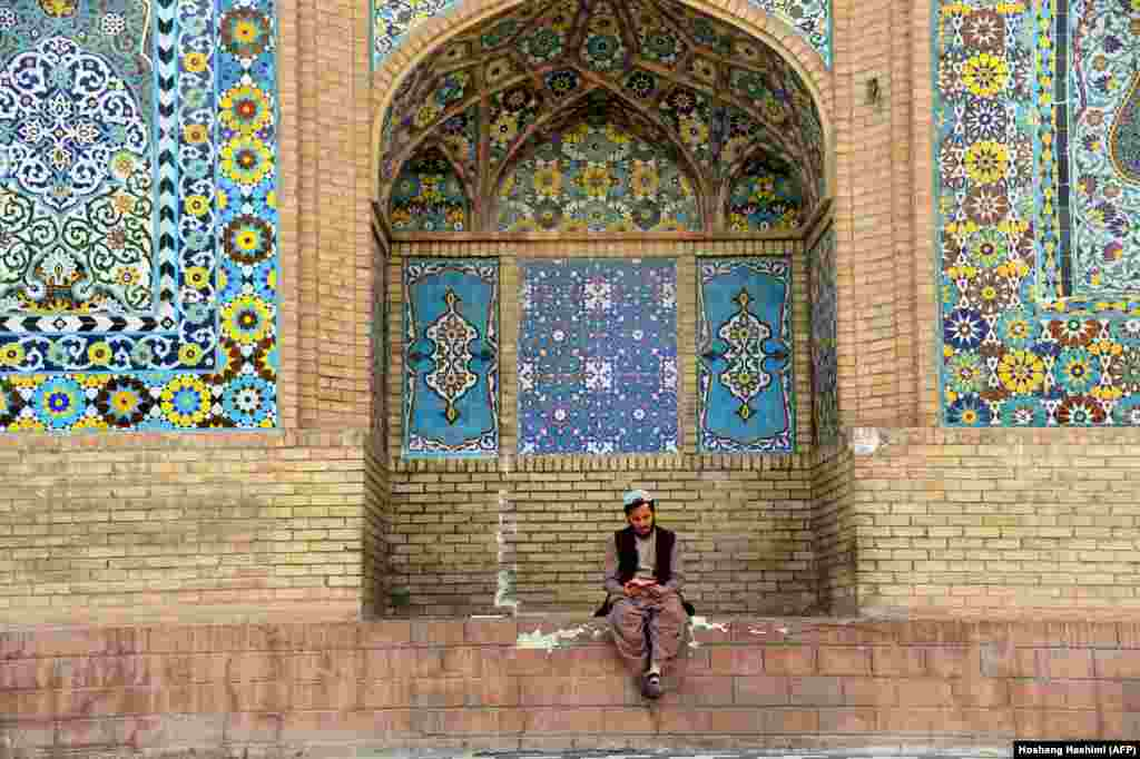 An Afghan Muslim reads the Koran outside a mosque during the holy month of Ramadan in Herat Province. (AFP/Hoshang Hashimi)