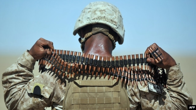 A U.S. Marine removes a bandolier of ammunition from around his neck during a group shooting lesson for Afghan police in Helmand Province.