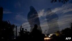 На окраине города Игуала полицейские охраняют место, где были захоронены десятки тел. 4 октября 2014