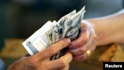 Покупатель передает продавцу банкноты номиналом 10 юаней. 12 августа 2015 года.
