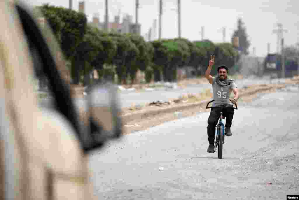 Syria -- A civilian riding a bicycle gestures towards a vehicle of the Syrian Democratic Forces (SDF) fighters in the Raqqa's al-Sanaa industrial neighbourhood, June 14, 2017