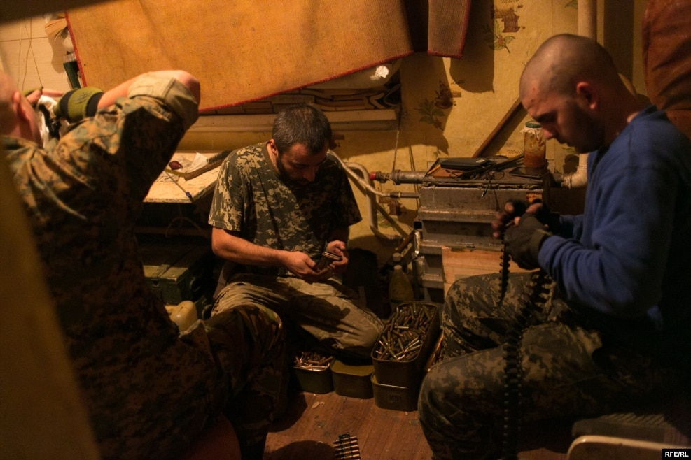 The volunteers prepare their weapons after intelligence reports indicate a heavy night of fighting lies ahead. On the left is Avram, an Orthodox Jew from western Ukraine. The Russian media has portrayed Ukraine's leaders as fascists, but he says he has never experienced anti-Semitism in his country.