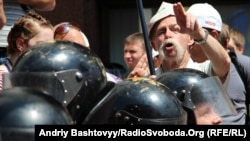A protester objecting to the Russian-language bill gestures over the heads of riot police in downtown Kyiv on July 5.