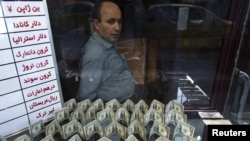 A currency exchange dealer sits at his shop as he waits for customers in Tehran's business district.