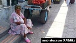 Turkmenistan. women sits at road-side