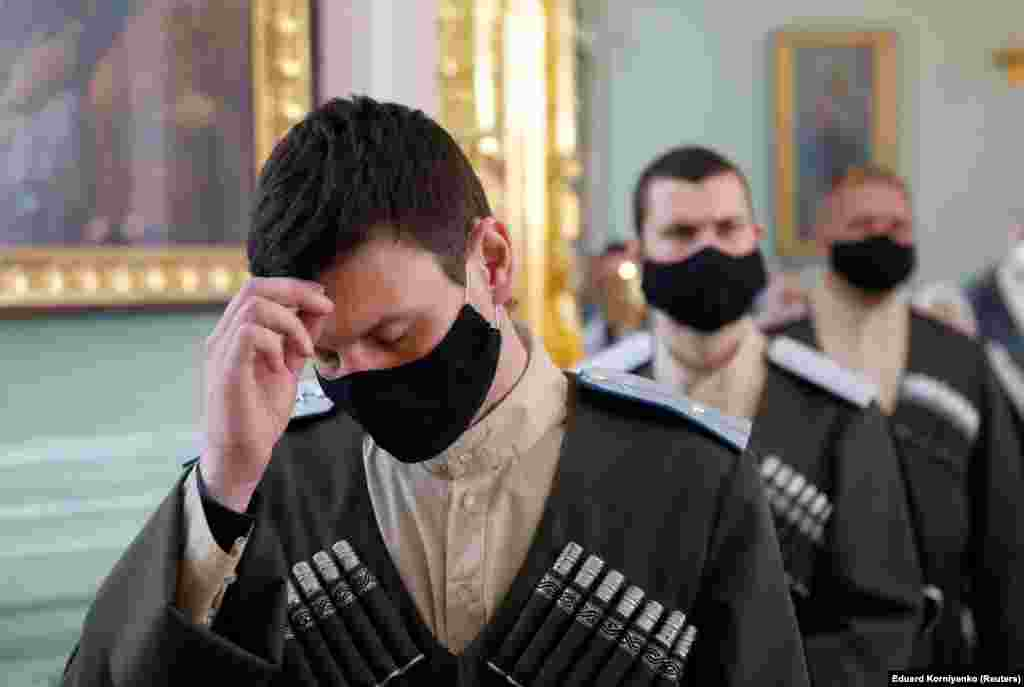 Cossacks wearing protective face masks pray during a service in Stavropol, Russia, on the eve of Orthodox Easter.