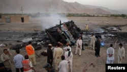 Police and security officials gather near the wreckage of a bus which was hit by a bomb attack in Balochistan.