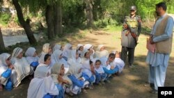A Security official stands guard as school girls attend their school in open air following the school building destruction by suspected militants, in Tirah valley, in Khyber tribal district. (file photo)