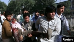 Afghanistan -- Men carry another man who was wounded during a suicide car bomb attack in Kabul, 11Jun2013