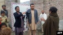 Преведувачот Забихула Тамана разговара со бегалци во Авганистан.