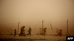 Syrian children walk around the camp grounds during a sandstorm at a temporary refugee camp in the village of Ayn Issa, housing people who fled the Islamic State group's Syrian stronghold of Raqqa.