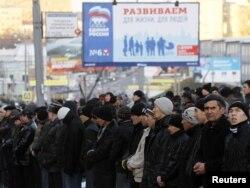 """Мусульмане в первый день мусульманского праздника Курбан Айт на фоне агитационного плаката партии """"Единая Россия"""". Москва, 6 ноября 2011 года."""