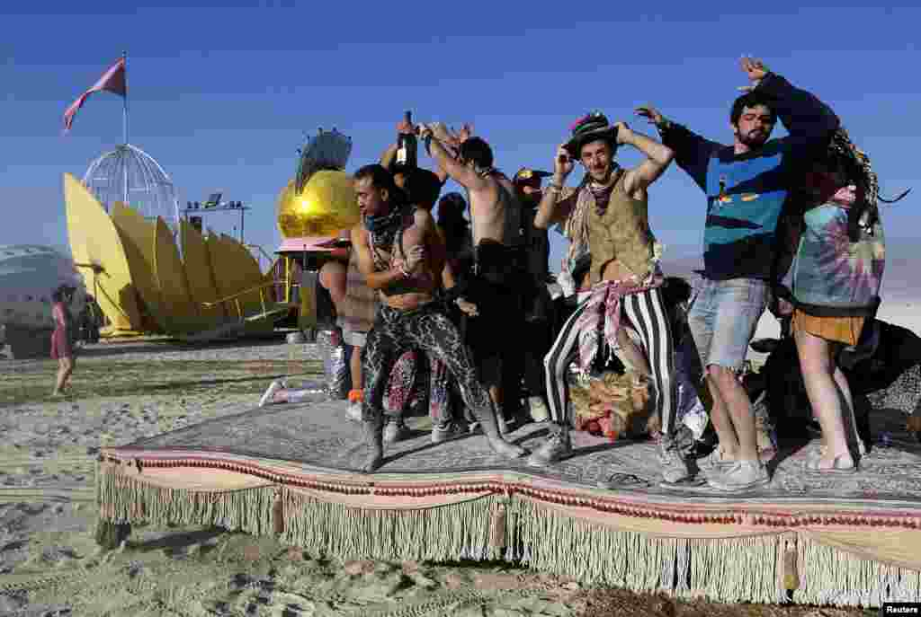 "Participants dance atop a moving ""hookah lounge"" art car at the 2013 Burning Man arts and music festival."