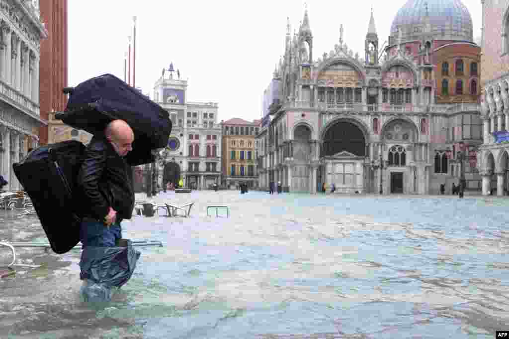 A man carries luggage across a flooded St. Mark's Square in Venice. Rain and wind hit the north of Italy on November 11, sparking flooding that reached 150 centimeters in the ancient city. (AFP/Marco Sabadin)