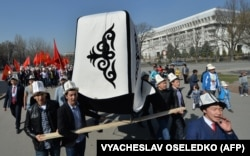 People wear kalpaks and carry a giant one and national flags during a rally on Flag/Kalpak Day in Bishkek on March 5, 2016.