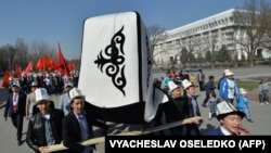 "Kyrgyz people wear traditional hats and carry a big Kyrgyz cap (kalpak) and national flags during a rally marking Kyrgyz Cap Day"" in Bishkek in March 2016."