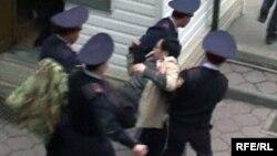 """Полицей Ермек Нарымбаевты """"Алға"""" партиясының кеңсесінен әкетіп барады. Алматы, 1 мамыр 2010 жыл."""