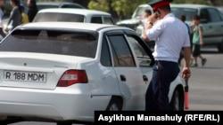 Сотрудник полиции подходит к остановленному автомобилю.